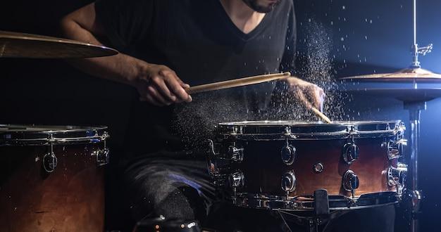 Um baterista toca bateria com baquetas em um quarto escuro.