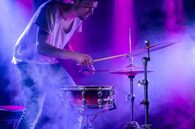 Um baterista toca bateria em um azul. belos efeitos especiais de luz e fumaça. o processo de tocar um instrumento musical.