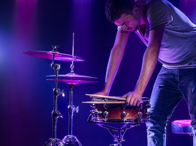 Um baterista toca bateria em uma parede azul