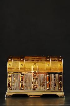 Um baú de ouro com joias em uma parede preta. espaço livre, conceito de riqueza. sutil.