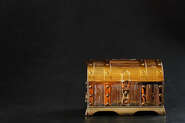 Um baú feito de ouro com joias em um fundo preto. espaço livre, conceito de riqueza. sutil.