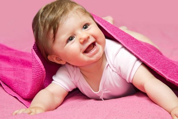 Um bebê adorável, rindo, olhando para a câmera