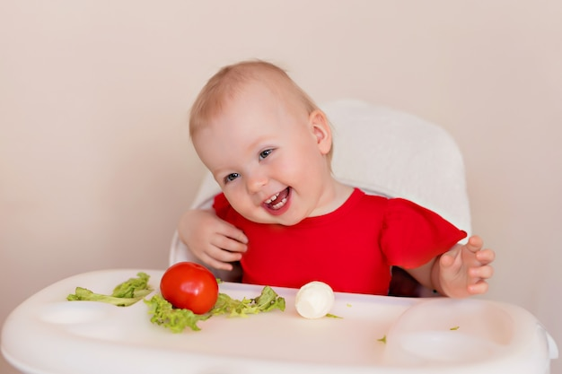 Um bebê alegre come legumes