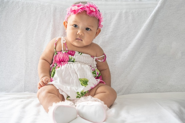 Um bebê aprende a se sentar em uma cama branca