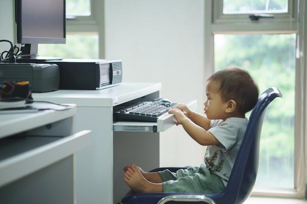 Um bebê asiático tentando usar o computador desktop
