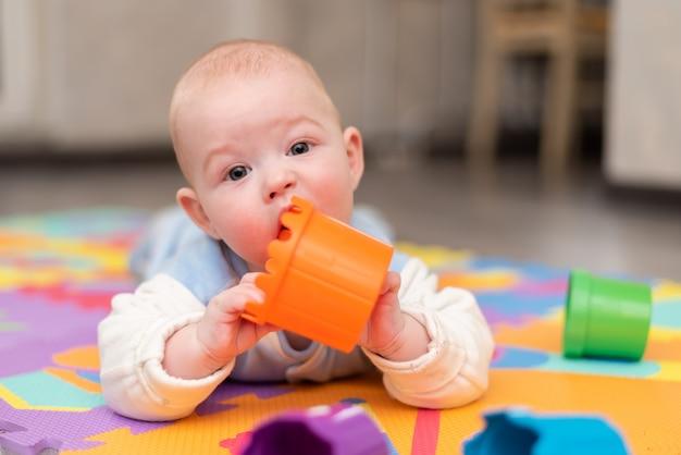 Um bebê brinca no chão. a criança está deitada de bruços no tapete com uma pirâmide. a criança pega um brinquedo na boca e lambe-o. dentição em uma criança.