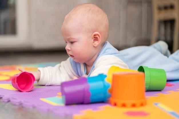 Um bebê brinca no chão. a criança está deitada de bruços no tapete com uma pirâmide.
