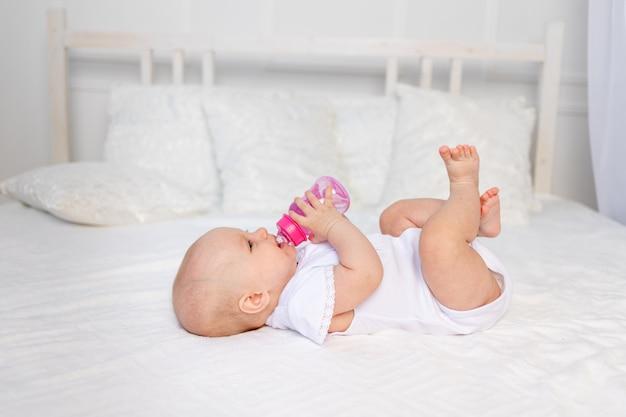 Um bebê de 6 meses encontra-se em uma cama branca e bebe leite de uma garrafa, conceito de comida para bebê, espaço de texto