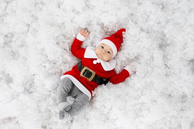 Um bebê de cinco meses em uma roupa de papai noel está deitado de costas na neve e sorri