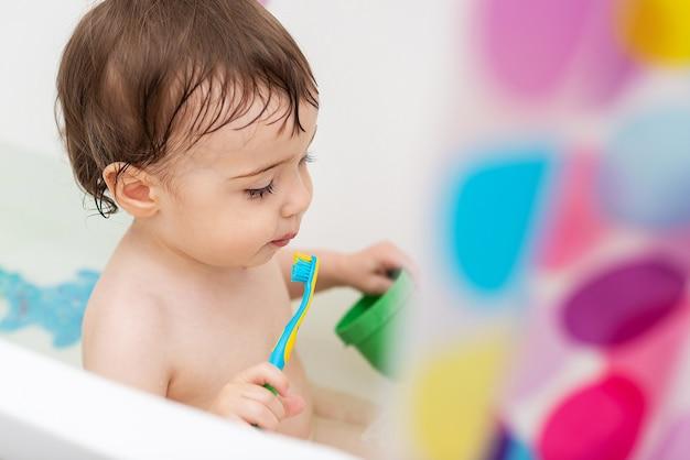 Um bebê de um ano se lava na banheira, brinca com brinquedos e aprende a escovar os dentes