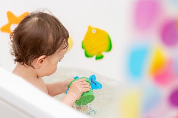 Um bebê de um ano se lava na banheira e brinca com brinquedos