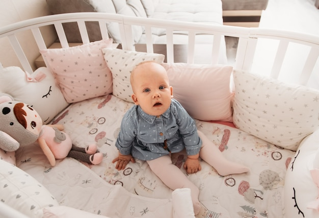 Um bebê menina bonita senta-se em um berço. uma olhada na câmera. bebê em um berço