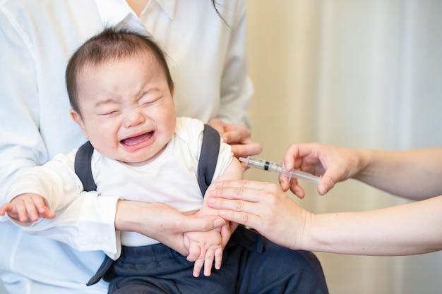Um bebê que é vacinado enquanto é segurado pela mãe