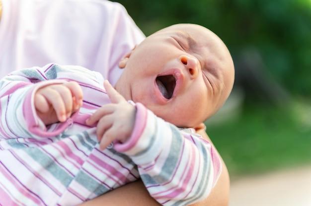Um bebê recém-nascido bocejando nos braços da mãe
