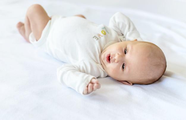 Um bebê recém-nascido deita em uma cama branca