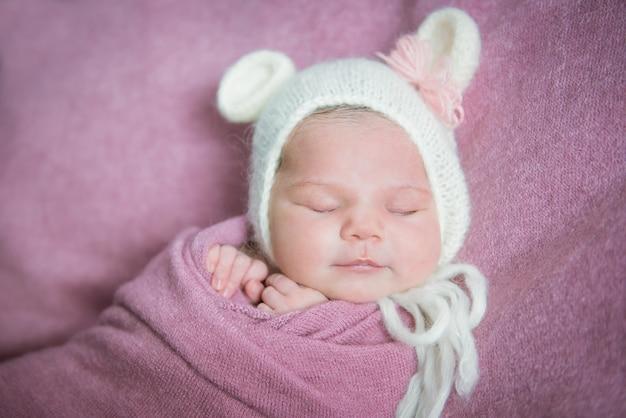 Um bebê recém-nascido dorme com um chapéu e orelhas em um cobertor rosa