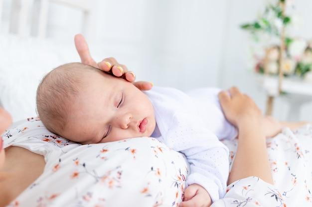 Um bebê recém-nascido dorme sobre a mãe, um sono saudável conjunto de mãe e bebê