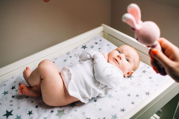 Um bebê recém-nascido e os pais são brincados com um brinquedo infantil. uma criança encontra-se em um trocador. os primeiros anos de vida.