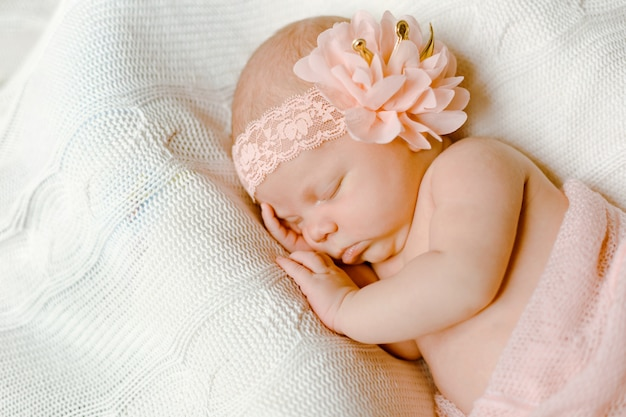 Um bebê recém-nascido encantador, envolto em um cobertor rosa suave