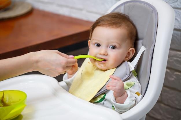 Um bebê sorridente de nove meses se senta em uma mesa branca em uma cadeira alta e come com uma colher de uma tigela. a mãe alimenta o bebê com uma colher. fundo desfocado. alimentação saudável para crianças. alimentos para crianças.
