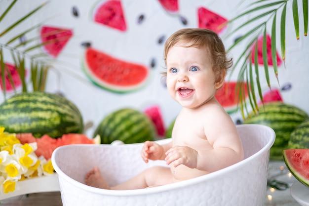 Um bebê, uma menina, um retrato em close-up em um fundo de melancias rindo e se alegrando