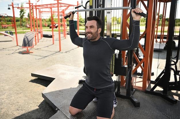 Um belo atleta de meia-idade pratica esportes, sacode os ombros e os músculos das costas em um simulador estacionário em um campo de atletismo