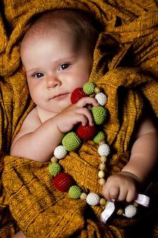 Um belo bebê está deitado com esferas com contas de malha