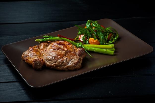 Um belo bife suculento com salada em um prato marrom direto está sobre a mesa.