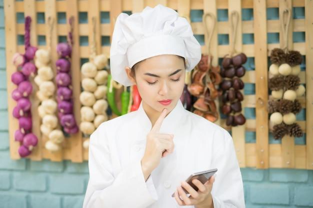 Um belo chef asiático está procurando um telefone celular na cozinha cheio de especiarias com o conceito de pedir comida por meio de um aplicativo em um smartphone.