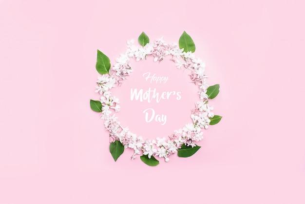 Um belo círculo de flores lilás e folhas no centro da inscrição feliz dia das mães.