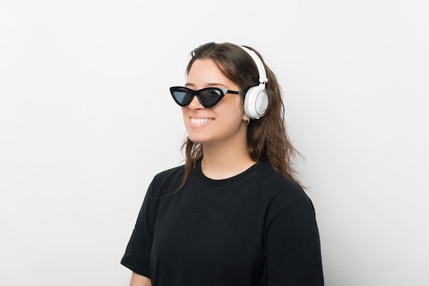 Um belo close-up retrato de uma jovem positiva ouvindo música enquanto usava óculos de sol