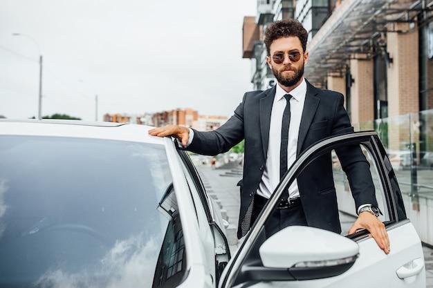 Um belo empresário de sucesso em terno completo abre seu carro nas ruas da cidade perto do moderno centro de escritórios