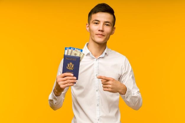 Um belo homem asiático em uma camisa branca apontando para um passaporte com passagens aéreas e dólares em dinheiro em um fundo amarelo