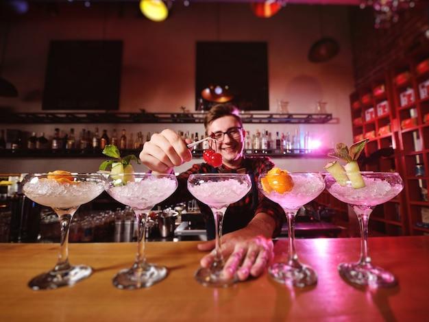 Um belo jovem barman prepara coquetéis e coloca cerejas para coquetéis