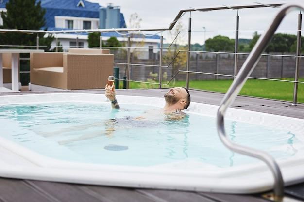 Um belo jovem brutal com um lindo sorriso segurando uma taça de champanhe e descansando na piscina
