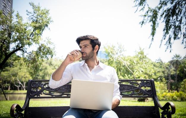 Um belo jovem empresário trabalhando com um laptop e bebendo café em um jardim