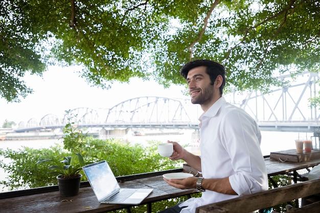 Um belo jovem empresário trabalhando com um laptop e bebendo café em uma cafeteria com fundo de ponte