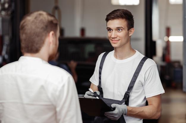 Um belo mecânico está conversando com seu cliente sobre o trabalho realizado.