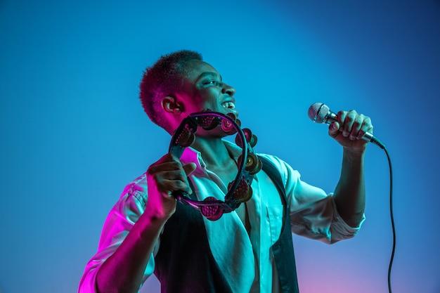 Um belo músico de jazz afro-americano tocando pandeiro e cantando