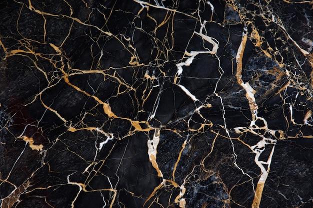 Um belo padrão na superfície de uma placa de mármore preto com veios amarelos e brancos chamado novo portoro.