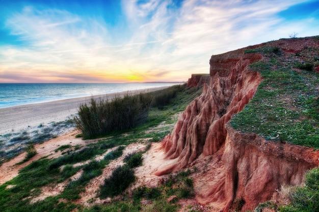 Um belo pôr do sol com encostas do mar e montanha.