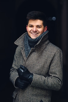 Um belo sorridente jovem de casaco quente e luvas de couro