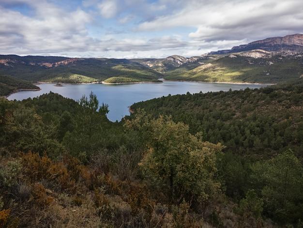 Um belo tiro largo de um pequeno lago cercado por árvores e vem nuvens na catalunha, espanha