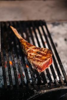 Um bife suculento é grelhado em um restaurante. assar carne no fogo na grelha.