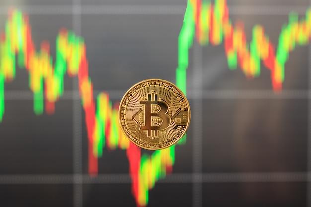 Um bitcoin com um gráfico borrado no fundo, o conceito de subida e descida dos preços