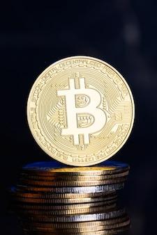 Um bitcoin de ouro em uma pilha de moedas. criptomoeda btc em um fundo escuro. dinheiro virtual de comércio eletrônico.