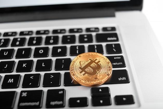 Um bitcoin dourado como cryptocurrency principal do mundo colocado no teclado do laptop.