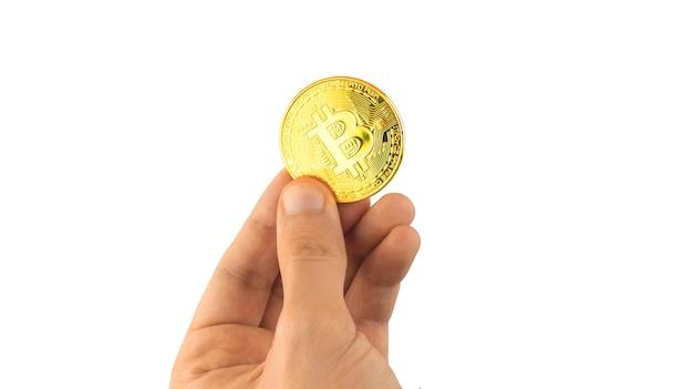 Um bitcoin na mão, isolado no fundo branco, conceito de pagamento e transferências de criptomoeda, foto de moeda de ouro da criptomoeda