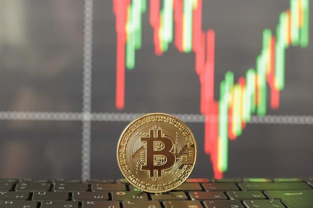 Um bitcoin no teclado e um gráfico do crescimento e queda nos preços