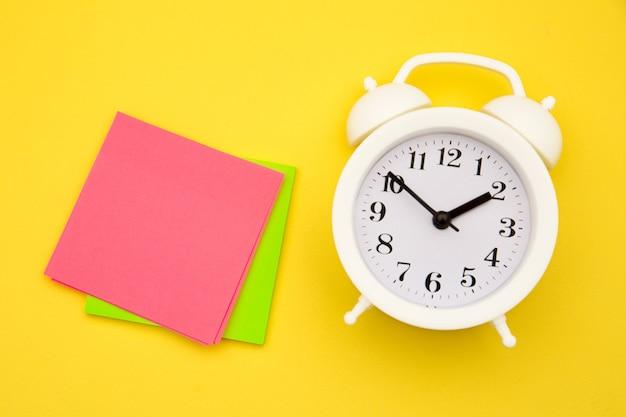 Um bloco de adesivos e um despertador branco em um papel amarelo.